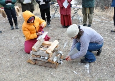 A Buddhist nun and lay people building a fire