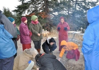 A group of people throwing sesame seeds onto a fire