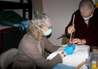 Venerable Chodron and Susan carefully and patiently fill a small Buddha statue.