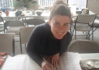 A woman, writing in a notebook, looks up at the camera