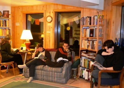 A group of people seated at desks and on couches, studying.