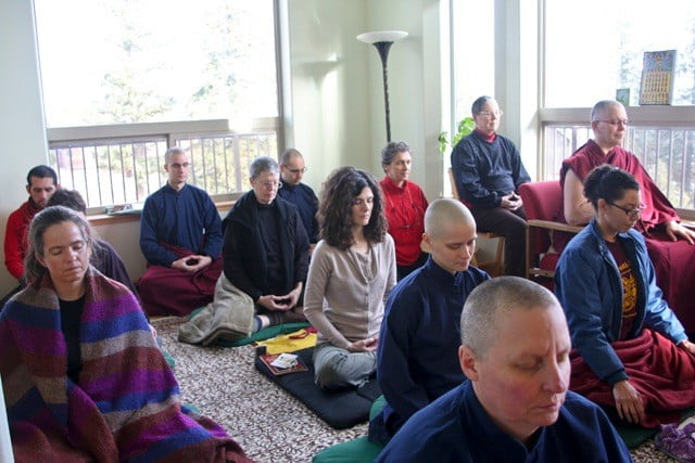 A group of people seated in rows, meditating
