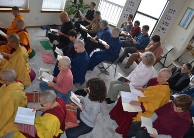 A group of people seated in rows read from books