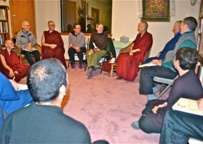 Buddhist nuns and lay people seated in a circle, in discussion