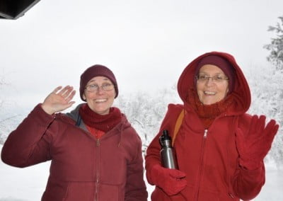 Venerables Chonyi and Semkye wave to the camera on a snowy day as they prepare to go to India.
