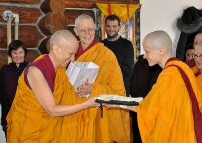 A radiant Venerable Jampa receives a welcoming gift from Venerable Thubten Chodron while monastics and guest observe the encounter.