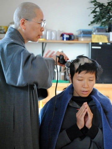 Venerable Jendy begins to shave Ruby's head.