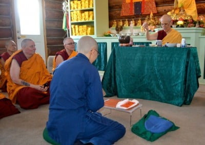 Ruby is seated on the floor before Venerable Chodron to receive her precepts.