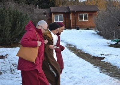 With very little snow and large tracks of ice, Venerables Thubten Chodron and Yeshe help Venerable Heng-ching to the car.