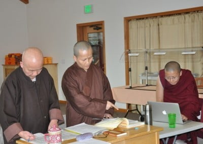 Venerables Heng-ching and Hong-fan, with Venerable Thubten Damcho's help, prepare English translations of the Varsa and Pravarana ceremonies that they will teach the Abbey sangha.