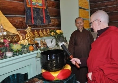 Venerable Thubten Jigme practices ringing the large gong as Venerable Hong-fan looks on.