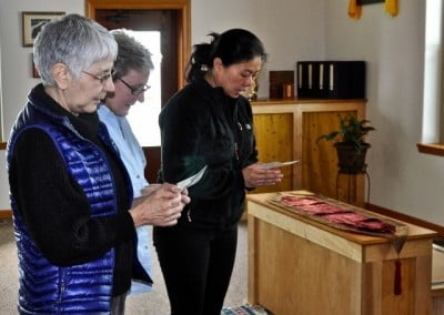 Tanya, Marga, and Cheng Cheng make a food offering to the sangha.
