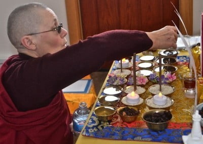 Venerable Chonyi sets up the many offerings in the Yamantaka retreat space.