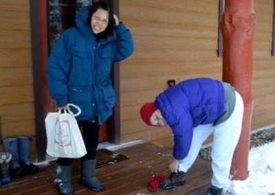 Lynda and Tanya put on their snow cleats before traveling on the snowy paths.