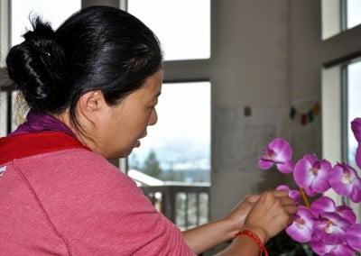 Cheng Cheng arranges beautiful artificial orchids for the altar.