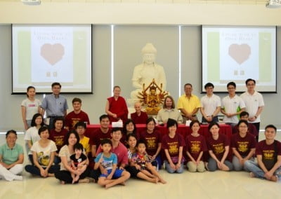 Students, some with children, gather for a group photo with Venerable Chodron.