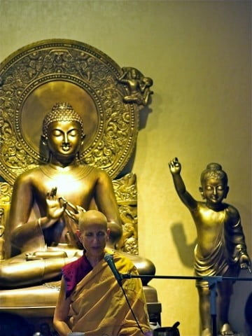Venerable Chodron in front of a statue of the Buddha.