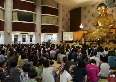 Venerable Chodron seated in front of a large statue of the Buddha, teaching.
