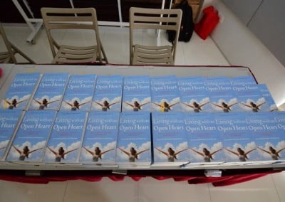 """Copies of """"Living With an Open Heart"""" arranged on a table."""