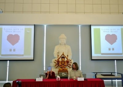 """Venerable Chodron on a dais, with displays of her book """"Living With an Open Heart."""""""