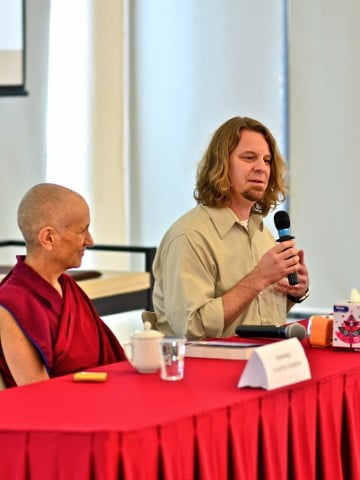Venerable Chodron on a dais with another speaker.