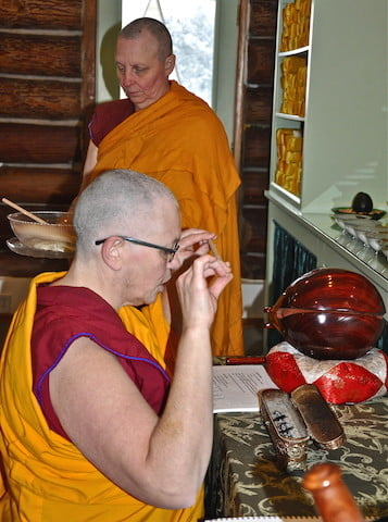 Venerable Yeshe offers the first stick to the Buddha.