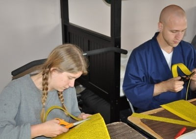 Cassidy and Byoghen focus quietly while cutting sheets of mantra that will later be rolled and placed into statues.