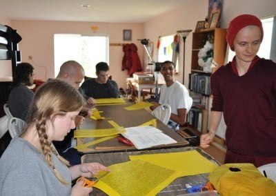Venerable Jampa guides the group through the careful process of cutting and rolling mantras that will be used in filling statues.