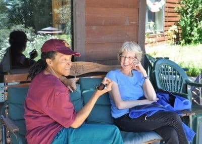 Cheryl and Julie, Abbey guests, sit on a cushioned bench outside Ananda Hall