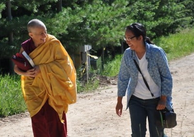 Venerable Chodron and Belinda share greetings as they walk to the hall.