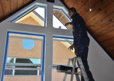 Nate paints the upstairs loft in Ananda Hall after new windows are installed.