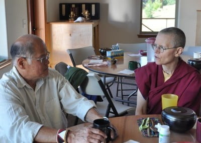 Venerable Thubten Tarpa and Matt, who faithfully mows the Abbey's grass in summer, discuss the recent windstorm and the damage that dislocated many of the people residing in a nearby trailer park.