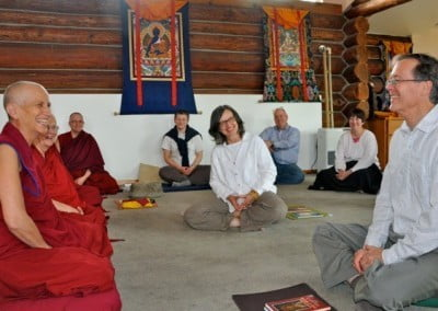 A couple sitting in front of Venerable Chodron and other lay people sitting around them, all of them are smiling happily.
