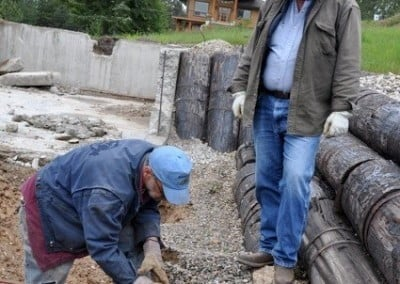 A man bending and removing the rebar from the old foundation, while another man is looking on.