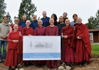 A group photo of Venerable Chodron, abbey sangha, three woman and a man, standing behind a banner that show the future Chenrezig Hall.