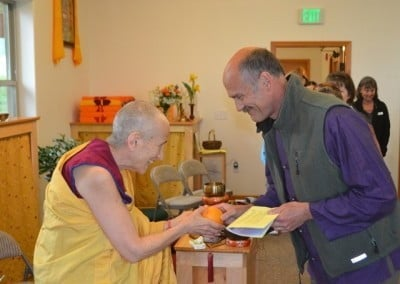 Venerable Thubten Chodron receives an offering from John.