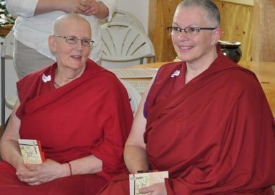 Venerables Thubten Jigme and Yeshe bask in the glow.