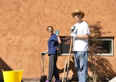 Alicia and Clint begin turning the soil in a new flowerbed in front of the hall.