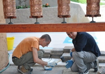 Nate and Loren place concrete pavers under the prayer wheels. The entrance to Chenrezig Hall now looks great.