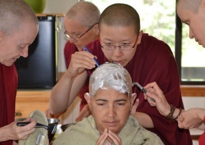 Venerables Samten, Damcho, and Jampa shave Alicia's head, with Venerable Semkye in the back.