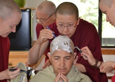 Buddhist nuns shave the had of a woman