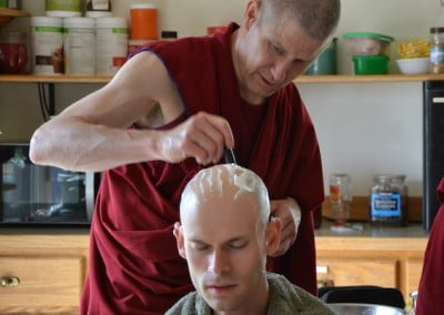 A Buddhist monk shaves the head of a young man
