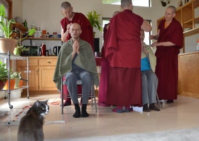 A cat sits and watches as a Buddhist monk shaves a man's head