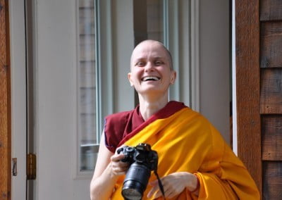 A Buddhist nun holding a camera laughs