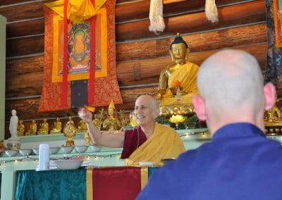 A Buddhist nun before a shrine throws petals