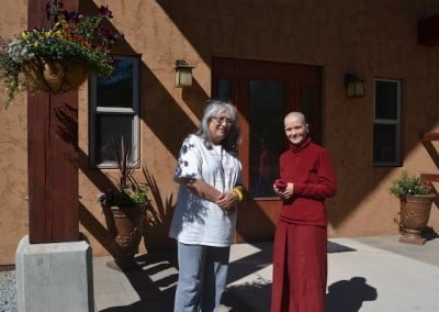 Cheri and Venerable Jampa chat by the beautiful flowering baskets and urns<br> that Cheri offered in front of Chenrezig Hall.