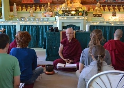 A Buddhist nun meditates with a group of meditators.