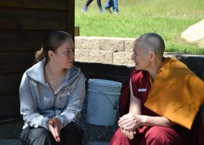 A Buddhist nun sits and talks with a lay woman