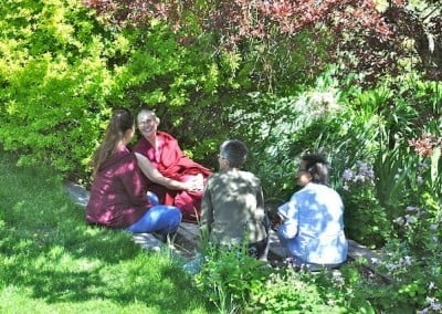 Venerable Chonyi and a group of participants share in the group discussion  in the flower garden.