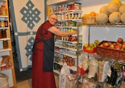Venerable Yeshe, our kitchen manager, finds a home for the abundant food offerings brought by the retreatants.
